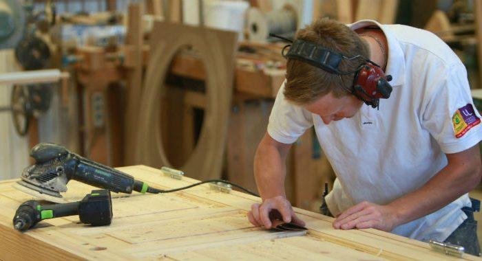 A male carpenter in white t-shirt sanding a wooden door.
