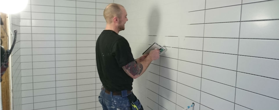 A man in a black shirt and blue pants tiling a bathroom.